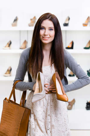 doubtfulness: Woman keeps two stylish shoes in the shopping mall and cant choose the one for her