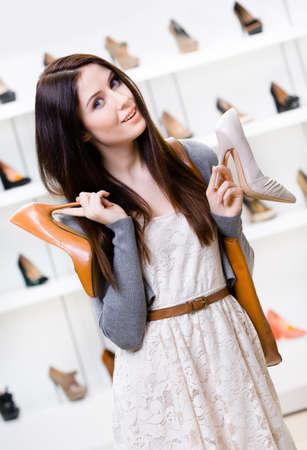 comprando zapatos: Mujer mantiene dos zapatos en el centro comercial y no puede elegir el indicado para ella