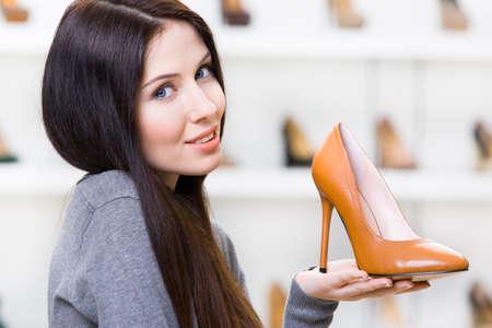 comprando zapatos: Retrato de mujer manteniendo cuero de zapatos de tacón marrón en el centro comercial