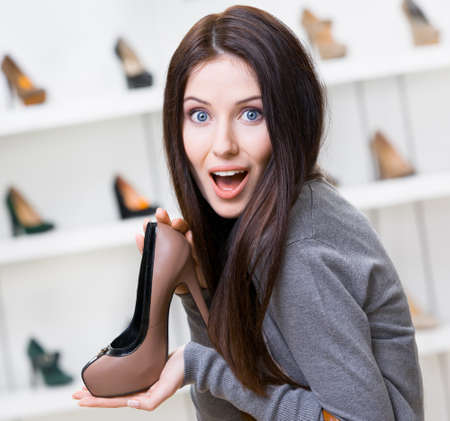 bargain: Portrait of woman keeping coffee-colored leather heeled shoe in shopping center