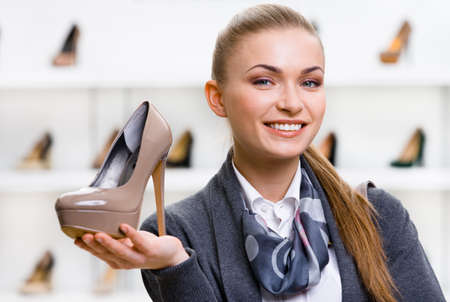 patent leather: Portrait of woman keeping coffee-colored shoe in shopping center against the showcase with footwear Stock Photo