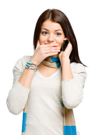 Teenager talking on phone and covering her mouth with hand , isolated on white photo