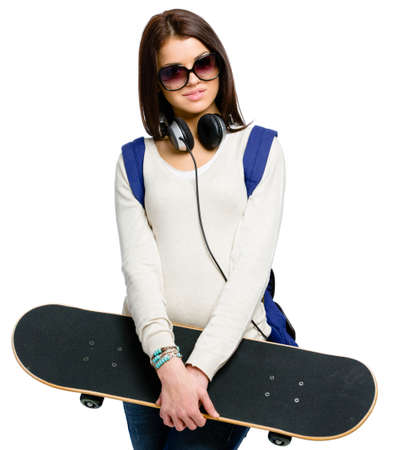 Half-length portrait of teenager with skateboard wearing sunglasses, earphones and rucksack, isolated on white. Concept of young generation Stock Photo - 22809168
