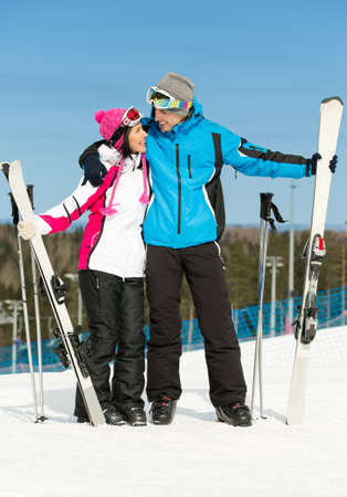 Full-length portrait of two embracing skiers with skis in hands photo