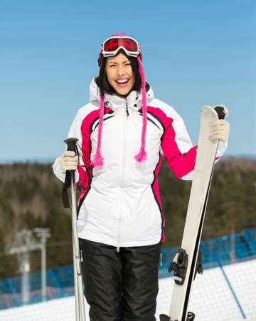 Half-length portrait of female skier standing with skis in hands. Concept of winter sports and cute entertainment photo