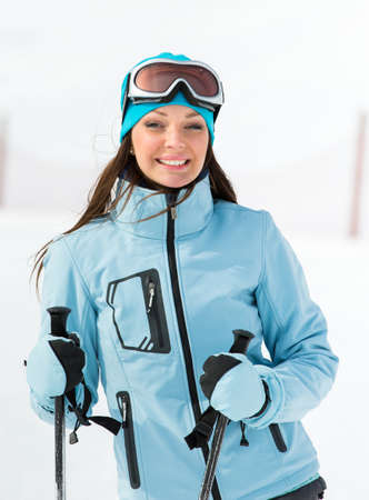Half-length portrait of female who goes skiing and wears goggles and sports jacket for winter sports photo