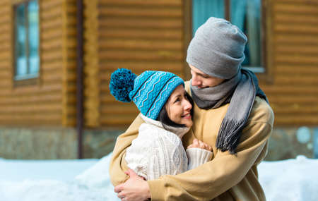 Half-length portrait of embracing couple outdoors during winter vacations photo