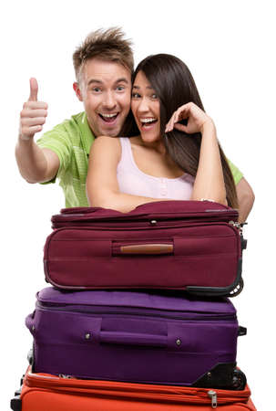 Couple stands near a pile of suitcases, isolated on white. Concept of romantic vacations and lovely honeymoon photo