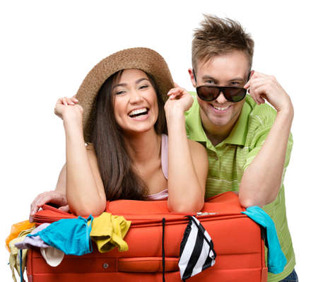 Couple packs up suitcase with clothing for trip, isolated on white. Concept of romantic vacations and lovely honeymoon photo
