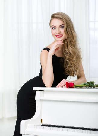 Brustbild der Frau im schwarzen Kleid stehend in der Nähe des Klavier mit roter Rose auf sie. Konzept der Musik und der Künste