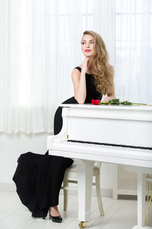 instrumentalist: Full-length portrait of woman in black dress standing near the piano with red rose on it. Concept of music and arts