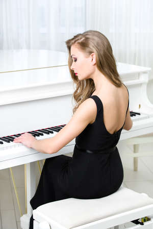the stool: Back view of woman in black dress sitting and playing piano. Concept of music and creative hobby Stock Photo