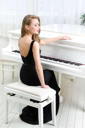 Portrait der Frau im schwarzen Kleid sitzt und spielt Klavier. Konzept der Musik und der Künste