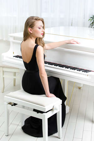 instrumentalist: Portrait of woman in black dress sitting and playing piano. Concept of music and arts