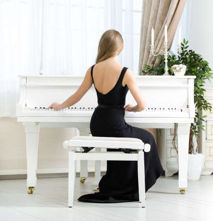 player bench: Back view of woman in black dress sitting and playing piano. Concept of music and arts