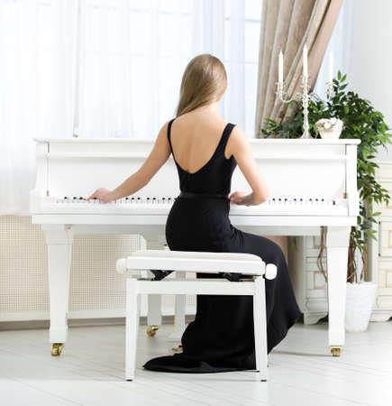 pianista: Vista posterior de la mujer en traje negro sentado y tocando piano. Concepto de la m�sica y las artes Foto de archivo