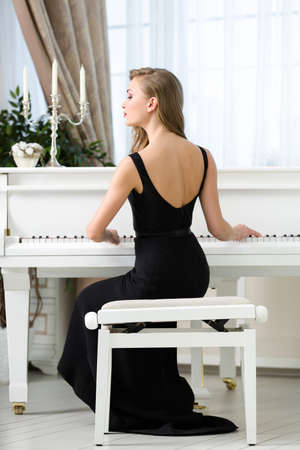 Back view of woman in black dress sitting and playing piano. Concept of music and entertainment photo