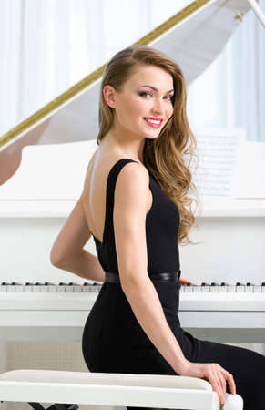 evening dress: Portrait of woman in black dress sitting at the piano. Concept of music and art