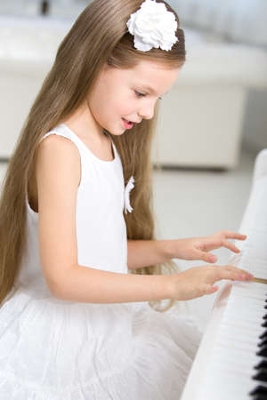 Portrait of little girl in white dress playing piano. Concept of music study and creative hobby photo