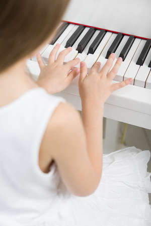 Back view of little girl in white dress playing piano. Concept of music study and arts Stock Photo - 22807731