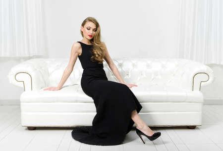 vestido de noche: Mujer sentada en el sofá de cuero blanco. Concepto de la belleza y la perfección