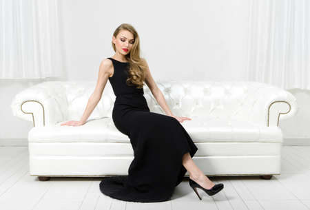 evening dress: Woman sitting on white leather sofa. Concept of beauty and perfection Stock Photo