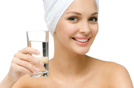 Close up of girl with towel on head hands glass of water, isolated on white. Concept of healthcare, beauty and youth photo