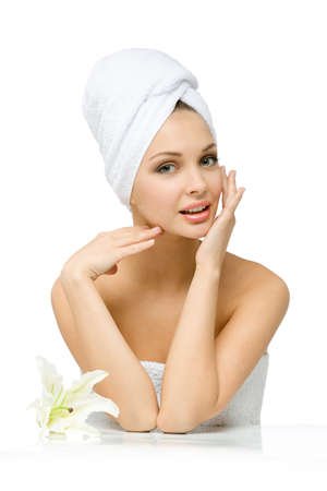 Naked girl with towel on head touches her face sitting near white lily, isolated on white. Concept of healthcare, beauty and youth photo