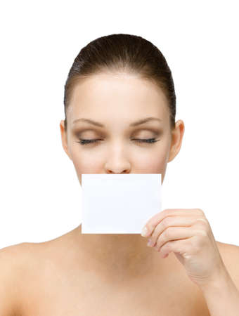 Nude girl with eyes closed hands white and blank copyspace card in front of her mouth, isolated on white photo