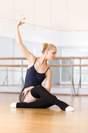 Ballet dancer works out sitting on the wooden floor in the classroom with barre and mirrors photo