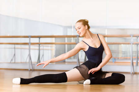 Bending ballet dancer stretches herself on the floor in the classroom