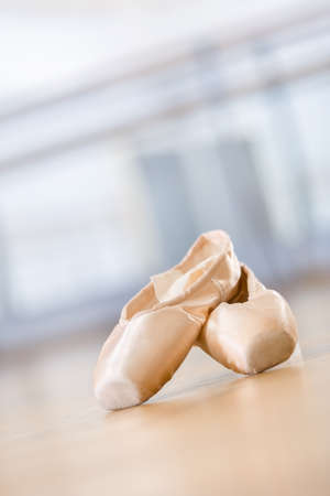 Close up shot of pointes for ballet lying on the wooden floor in classroom photo