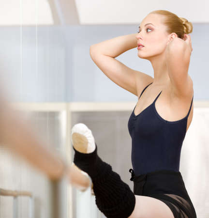 Female ballet dancer stretches herself near barre and mirrors in the classroom photo