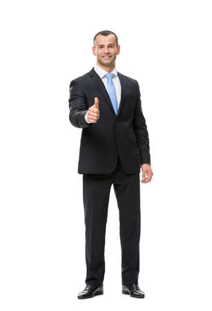 Full-length portrait of businessman who thumbs up, isolated. Concept of leadership and success photo