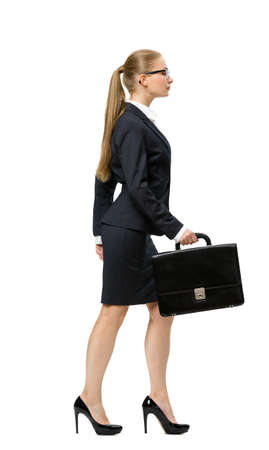 Profile of walking business woman handing case, isolated on white. Concept of leadership and success photo