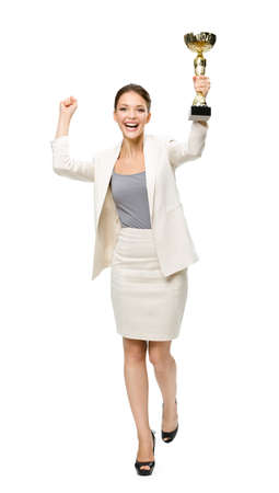 Full-length portrait of keeping golden cup business woman with hands up, isolated on white. Concept of victory and success photo