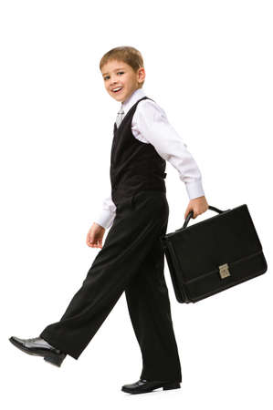 Full-length portrait of little businessman walking with black case in hands, isolated on white. Concept of leadership and success photo