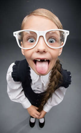 niña: Retrato de gran angular de la niña en gafas de lengua gesto, sobre fondo gris. Concepto de liderazgo y éxito Foto de archivo