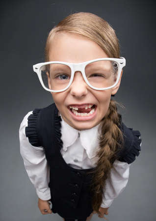 girl teeth: Wide angle portrait of little girl in glasses without front teeth, on grey background. Concept of leadership and success Stock Photo