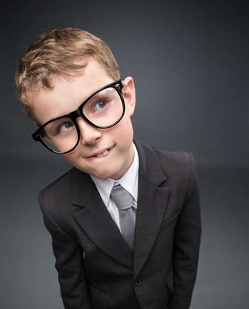 insight: Wide angle portrait of little pensive businessmen in glasses, on grey background. Concept of leadership and success Stock Photo
