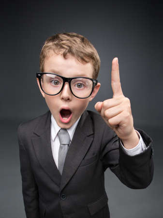 forefinger: Wide angle portrait of little businessmen in spectacles forefinger gesturing, on grey background. Concept of leadership and success Stock Photo
