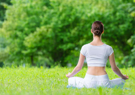 Backview of woman who sits in lotus position zen gesturing. Concept of healthy lifestyle and relaxation Standard-Bild