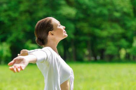 plan �loign�: Profil de femme avec les bras tendus et les yeux ferm�s. Concept de mode de vie sain et de d�tente