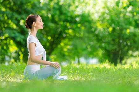 Profile of woman who sits in asana position. Concept of healthy lifestyle and relaxation photo