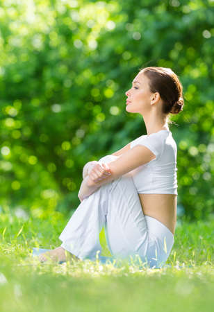 Profile of woman sitting on mat in park after exercising. Concept of healthy lifestyle and relaxation Stock Photo - 22807531