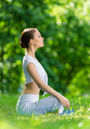 side profile: Profile of woman who sits in lotus position. Concept of healthy lifestyle and relaxation