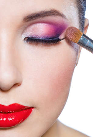 Close up of half-face of girl with brush applying bright pink makeup on eye, isolated on white photo