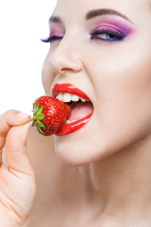 Close up of girl with bright pink make-up and red lips eating strawberry, isolated on white. Concept of beauty and healthy food Stock Photo - 22809565