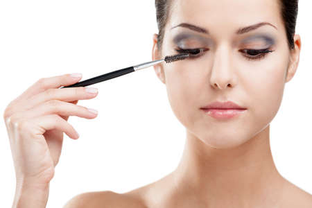 Woman putting on make up with cosmetic brush, isolated on white. Beauty procedures photo