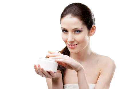 Woman holding lifting cream container and starting to apply cream, isolated on white photo